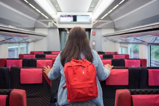 Mulher da trouxa do viajante que está no trem da velocidade. Foto Premium