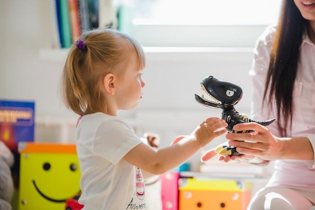 Mulher dando dinossauro para garota Foto gratuita