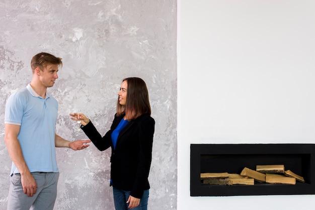 Mulher dando um conjunto de chaves para um homem Foto gratuita