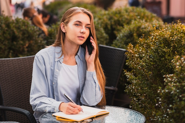 Mulher de alto ângulo, anotando na agenda Foto gratuita