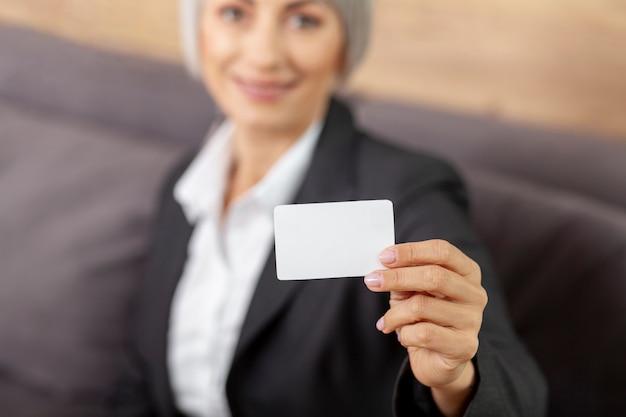 Mulher de alto ângulo, apresentando cartão de visita Foto gratuita