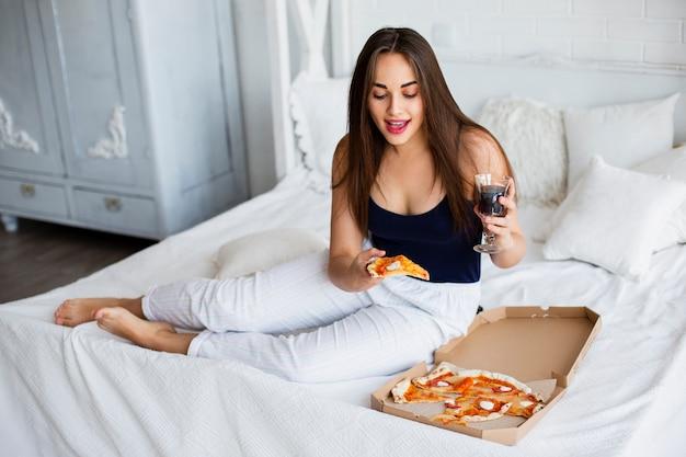 Mulher de alto ângulo em casa comendo pizza Foto gratuita