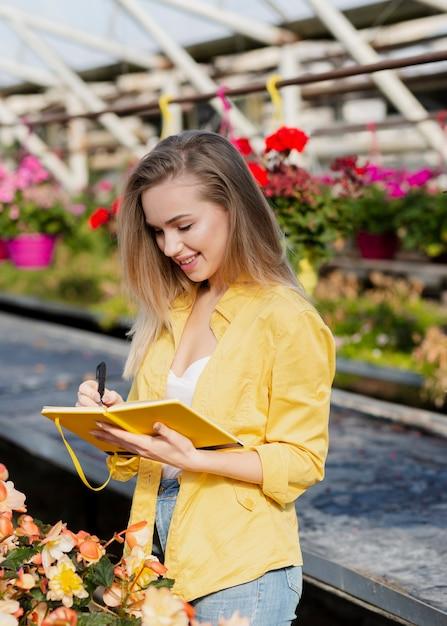 Mulher de alto ângulo, escrevendo na agenda Foto gratuita