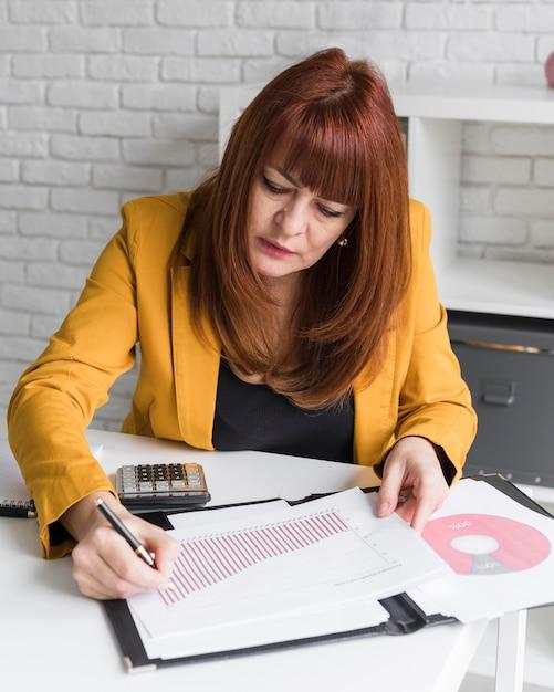Mulher de alto ângulo, escrevendo na folha de papel Foto gratuita