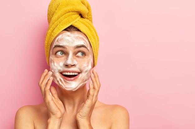 Mulher de aparência agradável e satisfeita usa sabonete líquido no rosto, mima a pele, remove a sujeira, parece revigorada e feliz, fica nua dentro de casa, usa uma toalha amarela enrolada na cabeça Foto gratuita