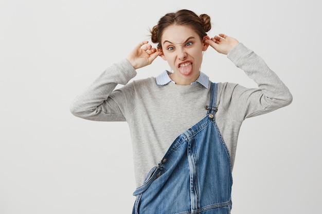 Mulher de aparência engraçada, vestindo macacão jeans fazendo careta fazendo orelhas salientes. atrevida rebelde feminina com penteado moderno sendo louco brincando. merriment, conceito divertido Foto gratuita