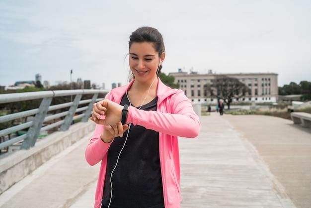 Mulher de aptidão verificando o tempo no relógio inteligente. Foto Premium