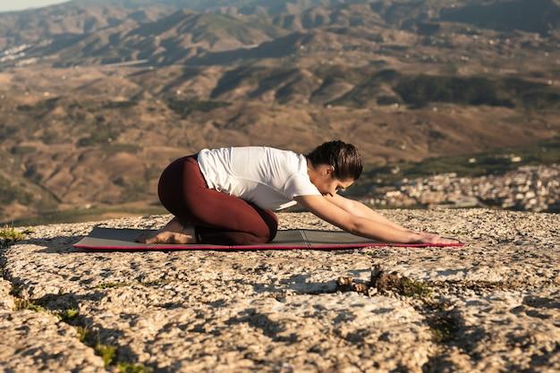 Mulher de baixo ângulo na esteira praticando ioga Foto gratuita