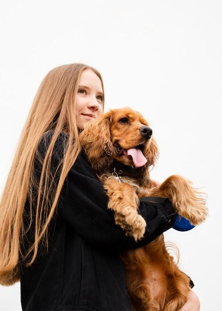 Mulher de baixo ângulo, segurando seu cachorro Foto gratuita