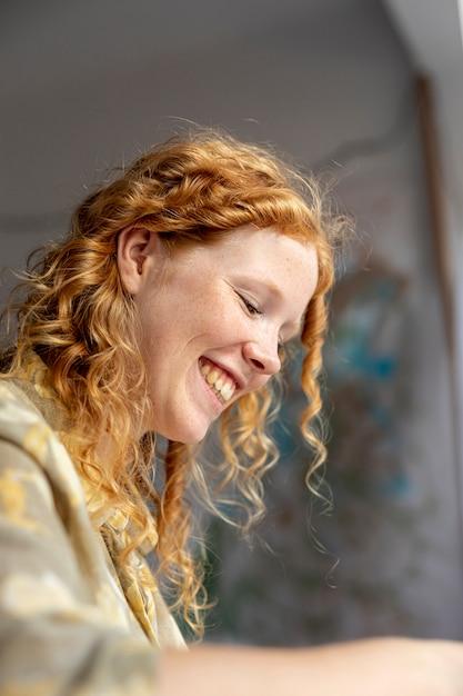 Mulher de baixo ângulo smiley dentro de casa Foto gratuita