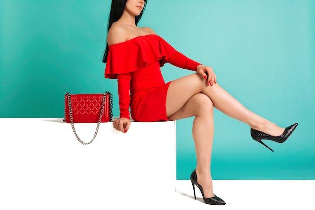 Mulher de belas pernas com vestido vermelho e bolsa de mão com sapatos de salto alto sentada no banco branco Foto Premium