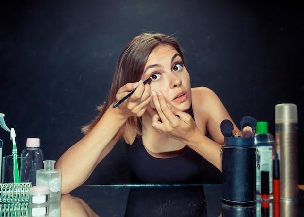Mulher de beleza aplicar maquiagem. menina bonita olhando no espelho e aplicar cosméticos com um pincel. Foto gratuita