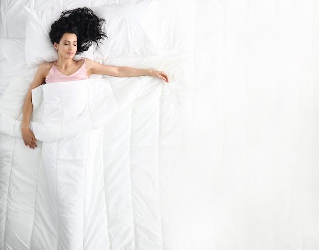 Mulher de beleza caucasiano jovem dormindo na cama branca Foto Premium