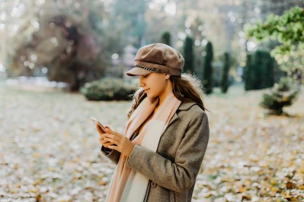 Mulher de beleza jovem escrever mensagem no celular em um parque de outono Foto gratuita