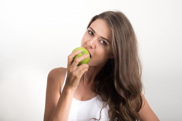 Mulher de beleza segurando a maçã verde enquanto isolado no branco Foto gratuita