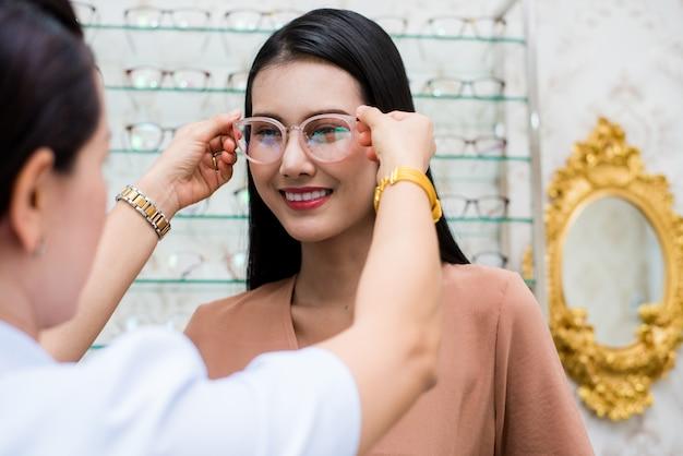 Mulher de beleza sorrir e usar óculos com optometrista. Foto Premium