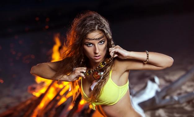 Mulher de biquíni posando perto de uma fogueira Foto gratuita