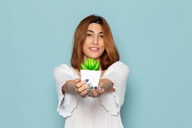 Mulher de blusa branca e jeans azul segurando uma pequena planta cor de senhora Foto gratuita
