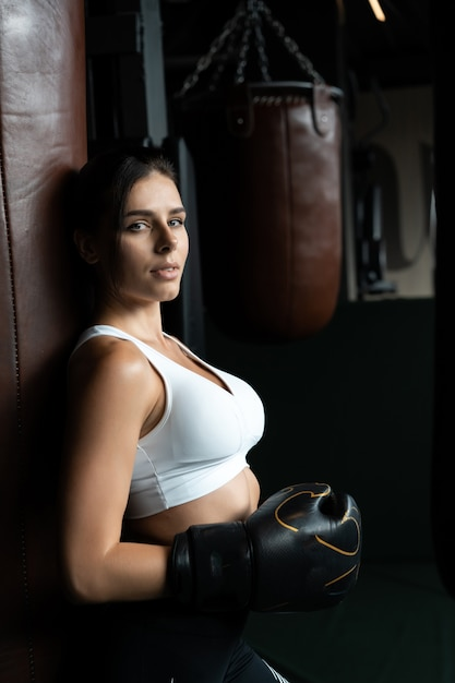 Mulher de boxe posando com saco de pancadas, no escuro. conceito de mulher forte e independente Foto gratuita