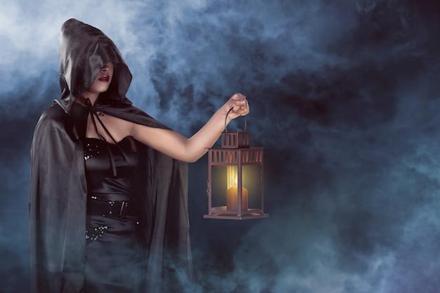 Mulher de bruxa de halloween segurando a lanterna com fundo de nevoeiro Foto Premium