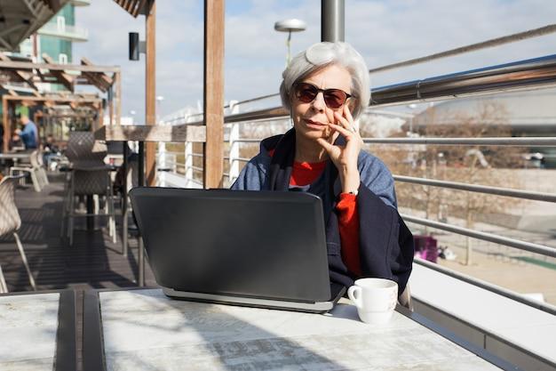 Mulher de cabelo cinza pensativa em óculos de sol usando laptop Foto gratuita