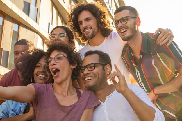 Mulher de cabelo encaracolado engraçada em copos tomando selfie Foto gratuita
