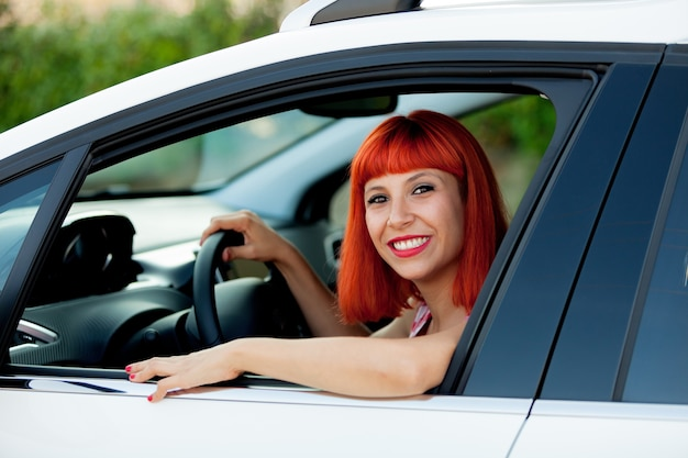 Mulher de cabelo vermelho com seu novo carro Foto Premium