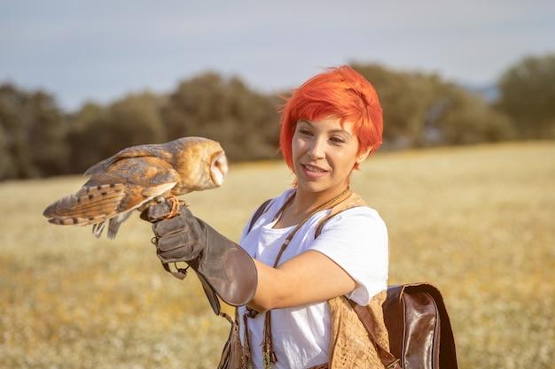 Mulher de cabelo vermelho com uma coruja branca no braço Foto Premium
