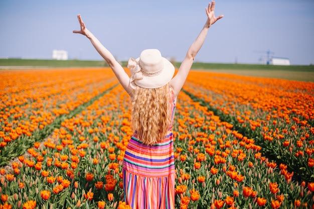 Mulher de cabelo vermelho em pé na parte de trás no campo de tulipa Foto Premium