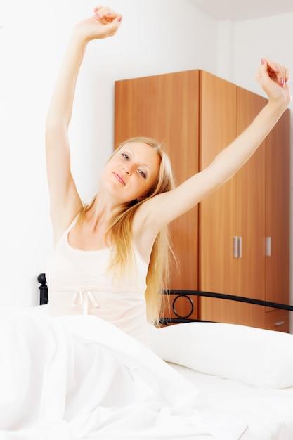 Mulher de cabelos compridos que acorda na folha branca Foto gratuita