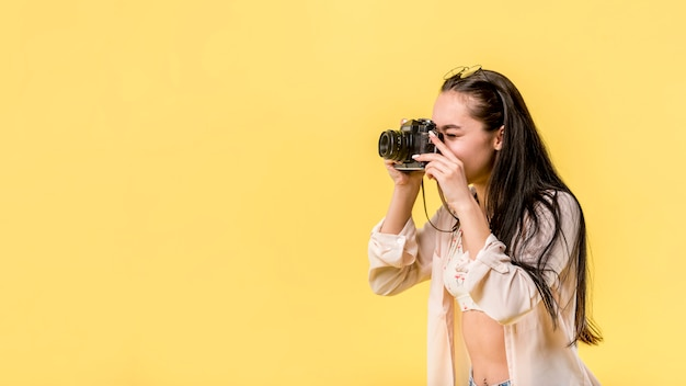 Mulher de cabelos compridos, segurando a câmera fotográfica e tirando foto Foto gratuita