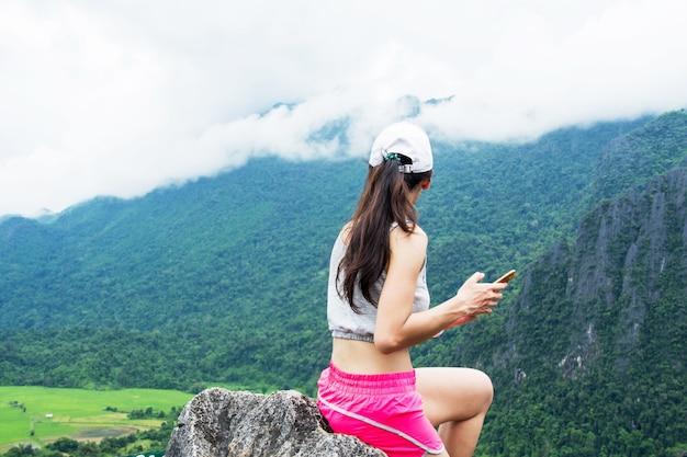 Mulher de caminhada traseira na montanha superior com opinião da natureza (vista superior de namxay em laos). Foto Premium