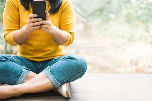 Mulher de camisa amarela, segurando um telefone móvel preto Foto Premium