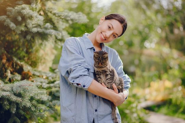 Mulher de camisa azul, brincando com gatinho fofo Foto gratuita