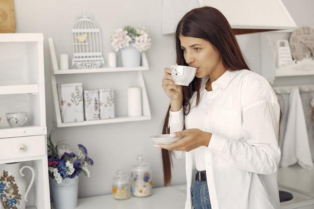 Mulher de camisa branca em pé na cozinha e tomando um café Foto gratuita