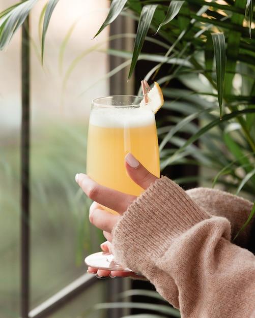 Mulher de camisa de inverno com um copo de suco de abacaxi pela janela. Foto gratuita