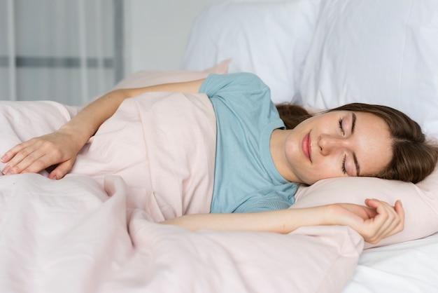 Mulher de camiseta azul dormindo Foto gratuita