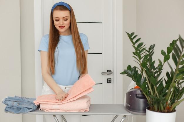 Mulher de camiseta azul passando em casa Foto gratuita