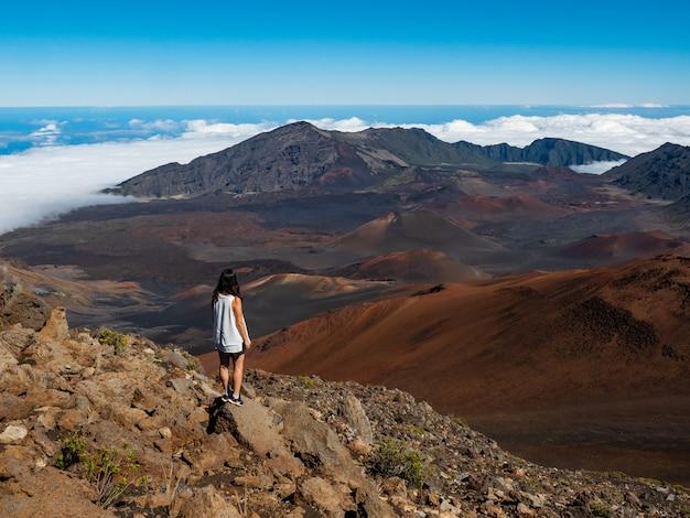 Mulher de camiseta branca e bermuda azul em pé na montanha de pedra marrom Foto gratuita