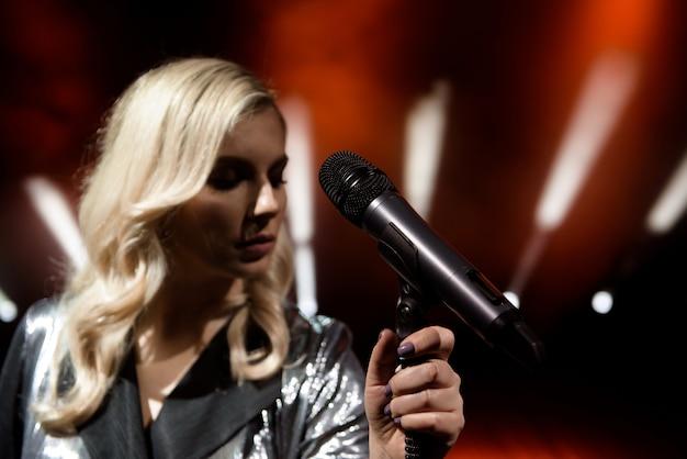 Mulher de cantor no palco. cantora e microfone. Foto Premium