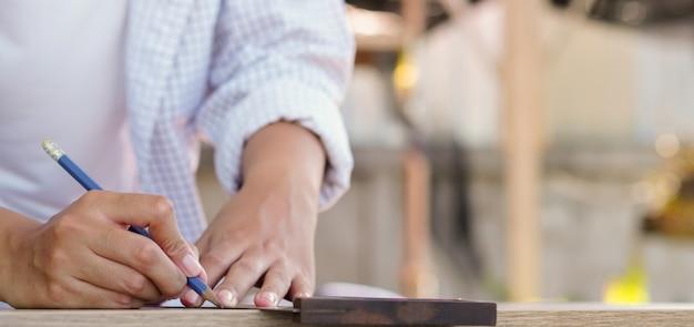 Mulher de carpinteiro usando régua para medir madeira em casa Foto Premium
