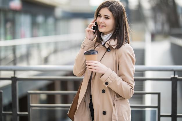 Mulher de casaco leve andando pela rua e falando ao telefone Foto gratuita