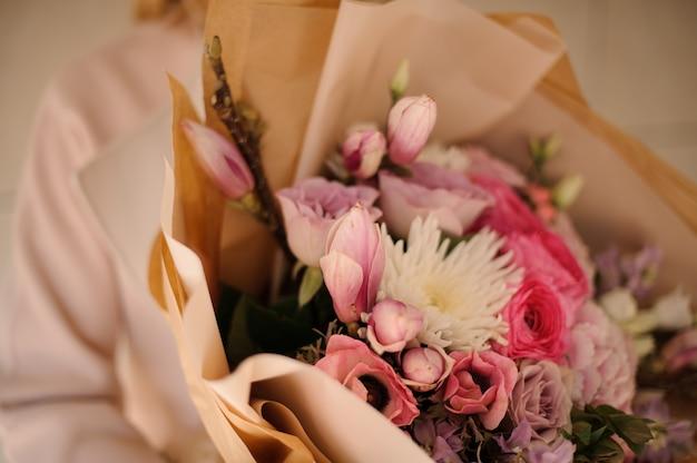 Mulher de casaco segurando um buquê de flores cor de rosa suave Foto Premium