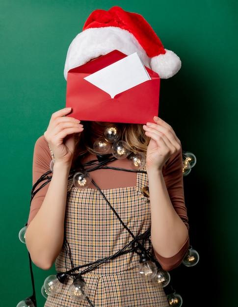 Mulher de chapéu de natal e correio em envelope Foto Premium