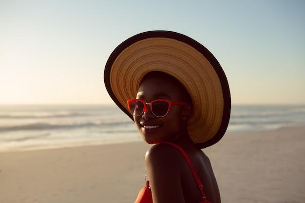 Mulher de chapéu e óculos de sol relaxantes na praia Foto gratuita