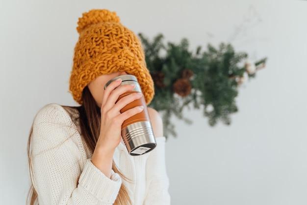 Mulher de chapéu laranja e caneca de metal termo reutilizável no dia de inverno do natal. vida sustentável Foto Premium
