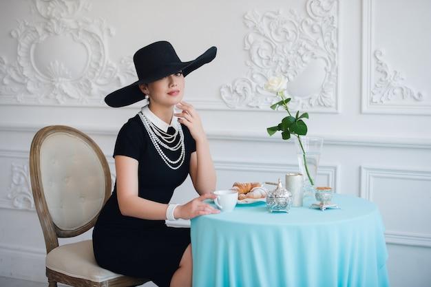 Mulher de chapéu, muito parecida com a famosa atriz, croissant comendo e bebendo chá. Foto Premium
