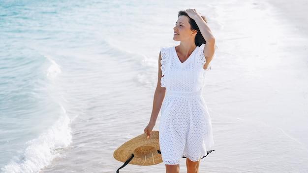 Mulher de chapéu na costa do oceano índico Foto gratuita