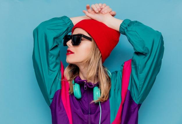 Mulher de chapéu vermelho, óculos escuros e terno dos anos 90 com fones de ouvido Foto Premium
