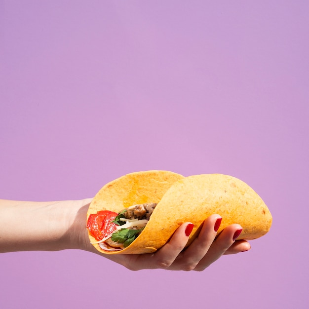 Mulher de close-up com burrito e fundo roxo Foto gratuita